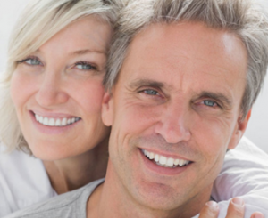 Smiling Couple With Dental Implants Improve Your Smile
